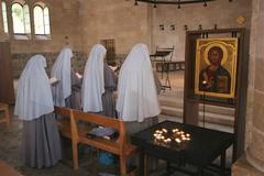 View of praying nuns inside The Church of the Multiplication of the Loaves and t - stock photo