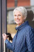 smiling senior woman exiting her house - stock photo