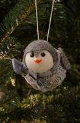 A Felt Gray Owl Christmas Ornament Hangs on a Fir Tree - stock photo