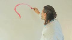 Artist painting a lightbulb idea sign Stock Footage