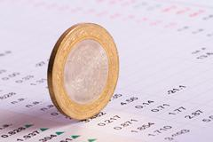Stock Photo of coin standing on financial data