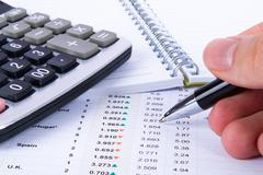 Stock Photo of hand holding pen and analyzing financial data