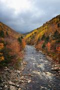 Fall colours on the Mackenzie River, Cabot Trail, Cape Breton, Nova Scotia. - stock photo