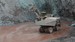 Dumper truck drives to earth mover in quarry Stock Footage