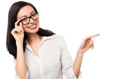 Woman adjusting her spectacles and pointing away - stock photo