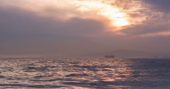 Ocean sunset with mountain and industrial equipment in distance 4k Stock Footage