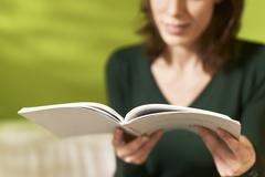 Girl studying literature with book at home Stock Photos