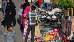 Street merchant sells textiles on the side of a busy road in India. Stock Footage