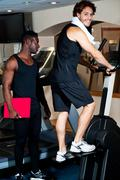 Stock Photo of Young guy with his personal trainer beside him