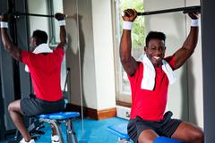 Confident young african guy working out in gym - stock photo
