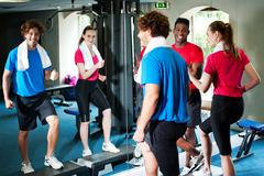 Stock Photo of Couple with personal fitness trainer in the gym