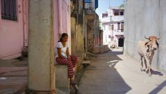 Young Indian woman sits in alley of village as sacred cow walks by in India. Stock Footage