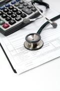 Calculator and stethoscope Stock Photos