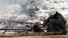 Soldier kindles bonfire Stock Footage