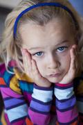 sulky little girl with head in hands - stock photo