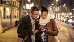 Tourist couple looking at map on smartphone in the city HD Stock Footage
