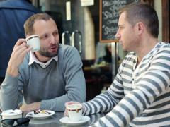 Two male friends drinking coffee and chatting in cafe NTSC Stock Footage