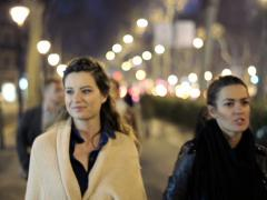 Two girls walking and talking in city at night NTSC Stock Footage