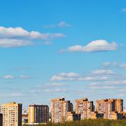Clouds in blue sky over brick apartment houses Stock Photos