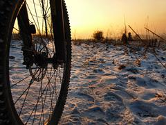 Front wheel and part of frame of mountain bike in the first snow on path - stock photo