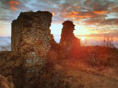 The stony ruin of medieval stronghold on the peak of rocky hill - stock photo