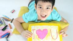 Portrait of a little asian happy boy painting Heart picture Stock Footage