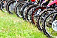 Stock Photo of motocross riders lined up before start on the race