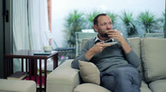 Man eating sandwich and drinking tea while sitting on sofa at home HD Stock Footage