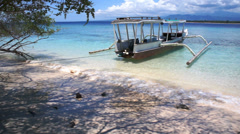 Soft wave of the sea on the sandy beach with boat, Gili Meno, Indonesia - stock footage