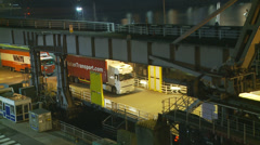 UK lorries driving on to ferry at night (speeded up) Stock Footage