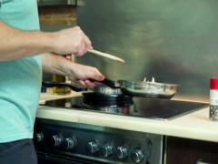 Man mixing vegetables on frying pan NTSC Stock Footage