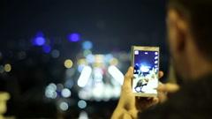 Man taking photo, beautiful view of Barcelona at night HD Stock Footage
