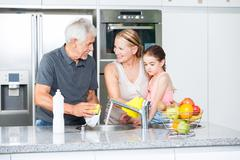 Grandparents and little girl washing dishes Stock Photos