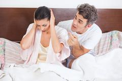 Unhappy couple in a bed, conflict problem Stock Photos