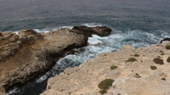 Sea moving in and out roughly against rocks islands stoney closer Stock Footage