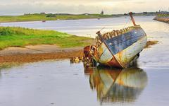 Stock Photo of boat wreck lying on the shore of lake