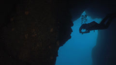 Diver swims back at the cave in blue water Stock Footage