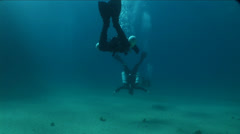 Divers swim in the blue waters of the island of Malta Stock Footage