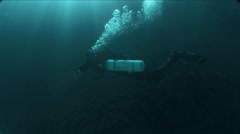 Diver swims lit by sunlight in the blue waters of Malta Stock Footage