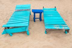 Two empty turquoise sunbeds at sandy beach. Stock Photos