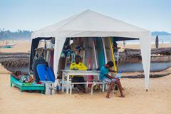 local men renting surf boards at weligama beach - stock photo