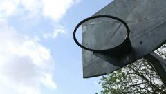 Tracking shot of a basketball hoop with the clouds in the background Stock Footage