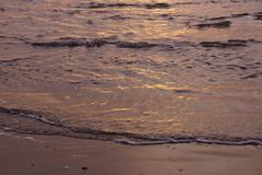 Textures of incoming surf at sunset Stock Photos