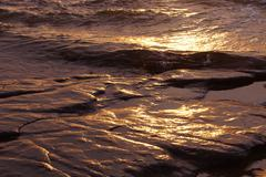 textures of incoming surf at sunset - stock photo