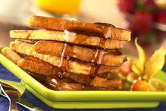 pouring maple syrup on french toast - stock photo