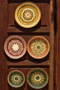 Pottery dishes in oriental style at wooden stand Stock Photos