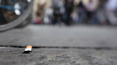 Stub of cigarette on the ground with people walking in the background. Stock Footage
