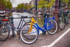 Bicycles lining a bridge over the canals of Amsterdam, Netherlan Stock Photos