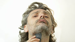 Man with electric shaver over white Stock Footage