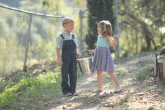 kids working on the farm  with a pail - stock photo